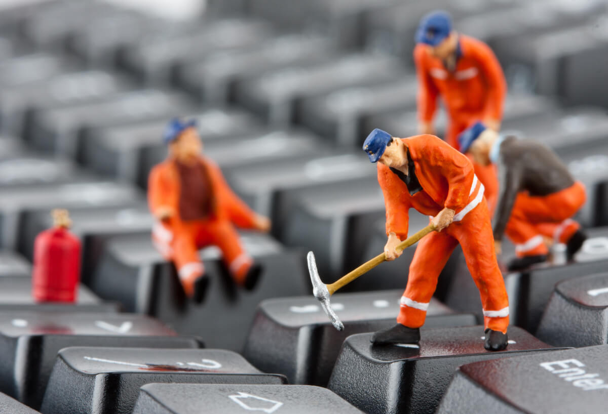 Close up of a computer keyboard with small figurines of workers repairing it