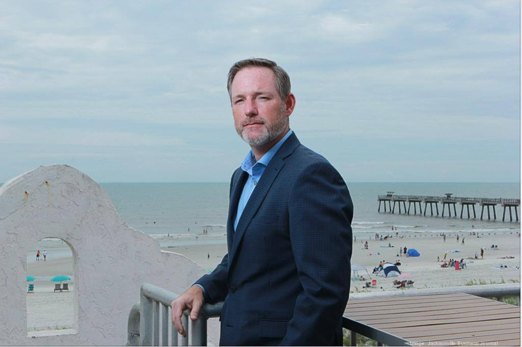 ICX President William 'Bill' Woody standing at a railing above a beach