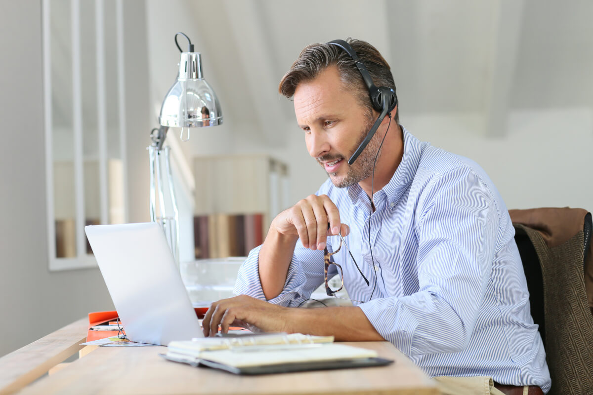 An older man working in his home office on his laptop while wearing a headset and holding his glasses in his right hand